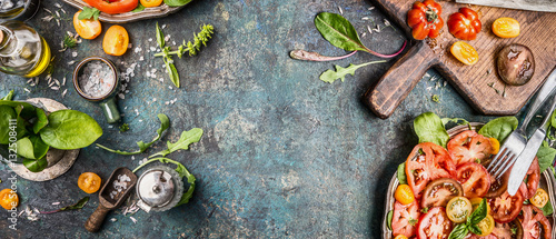 Fototapeta Healthy vegetarian salad making preparation with tomatoes on rustic background, top view, banner, copy space obraz