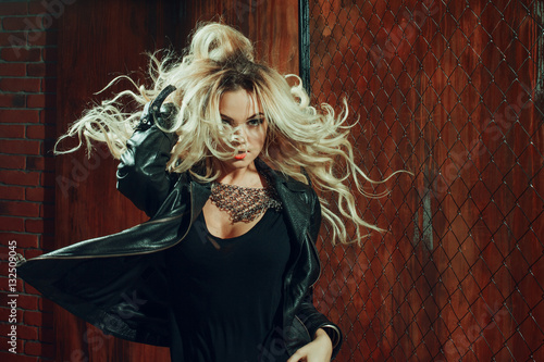Poster Pleine lune Rock'n'roll girl, young beautiful woman dances in dark alley, against the fence mesh