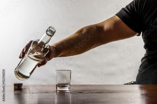 Poster de jardin Bar ein Mann sitzt an einem Tisch und gießt sich Schnaps in ein Glas