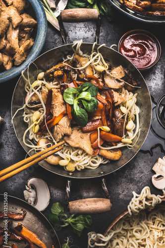 Photo  Asian dish with chicken vegetables noodles stir-fry in little wok with chopstick