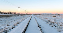 Snow Covered Train Tracks Into The Horizon At Sunset