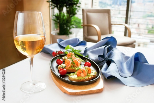 """Fotografía  Bruschetta with stewed salmon, cucumber and sauce """"Wasabi"""" and glass of white wi"""