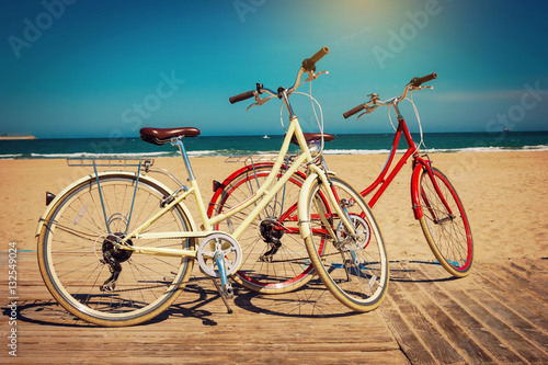 Velo Two retro bicycles on beautiful beach background