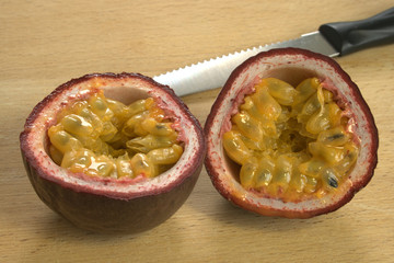 Cut open Passion Fruit or Maracuya, with knife on wooden background, backlit