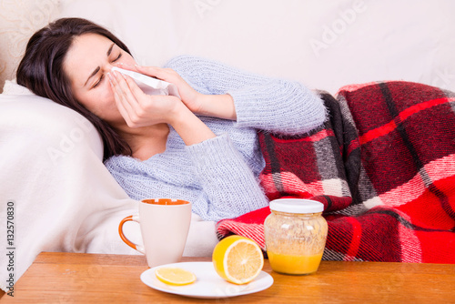 Fotografia, Obraz  Girl with cold lying under a blanket holding a tissue