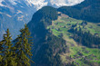View of landscape from cable car, Green field and snow-covered mountain in background in the Alps at Gimmelwald, Switzerland - April, 2016