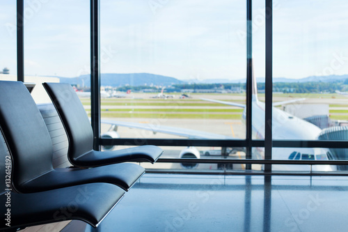 Foto op Aluminium Luchthaven airport background, chairs in waiting lounge and airplane in the window, interior