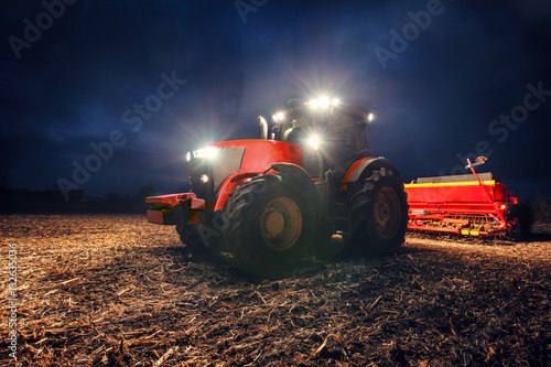 Tractor preparing land with seedbed cultivator at night плакат