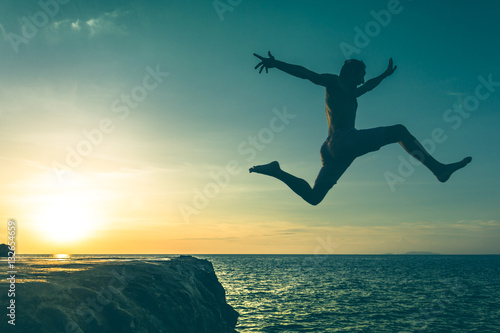 Photo  Fearless young man jumping over a cliff into the sea on sunset in Koh Phangan island, Thailand