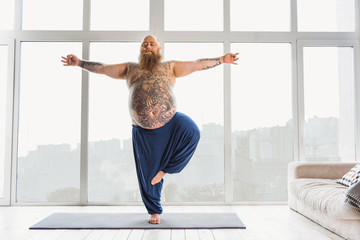 Naklejka Confident tattooed man practicing yoga