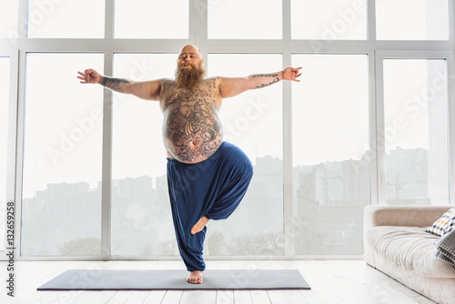 Confident tattooed man practicing yoga