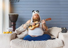 Man Playing The Guitar On His Couch