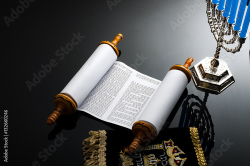 Religion and Judaism concept with the holy Torah and a menorah. The Torah is the jewish holy text / book and a menorah is the traditional branched candle stick specific to Hanukkah