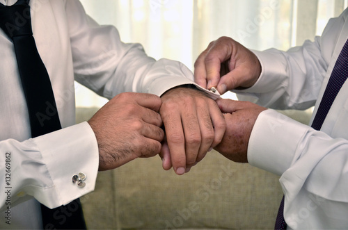 Fotografie, Obraz  Novio vistiéndose para casarse.