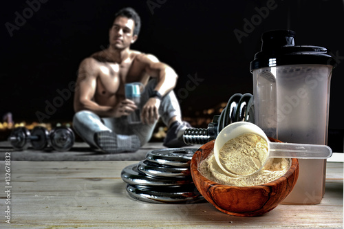Fotografia  Protein shake Vanilla flavor accompanied by weights and sportsme