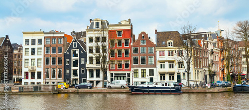 Traditional old buildings, canal and boat in Amsterdam, the Netherlands Canvas Print