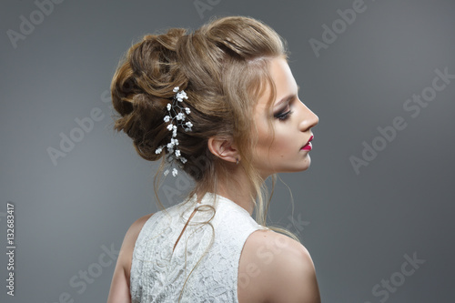 Elegant bride with a beautiful hairstyle and bright make-up isolated on a gray background.
