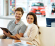 Beautiful young couple looking a new car at the dealership showroom