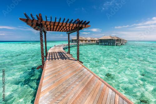 Obraz na płótnie Wooden jetty towards water villas in Maldives.