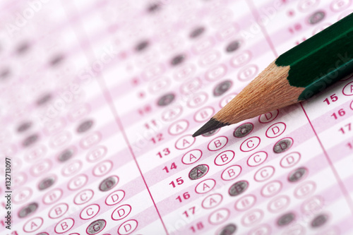 Fotomural Multiple choice exam paper with answers bubbled in and a green pencil resting on
