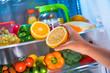 Woman takes the orange from the open refrigerator.