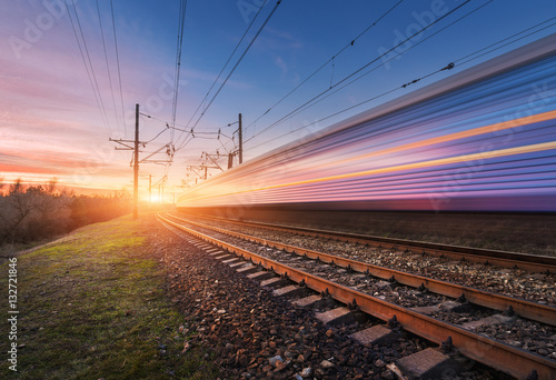 Foto  High speed passenger train in motion on railroad at sunset