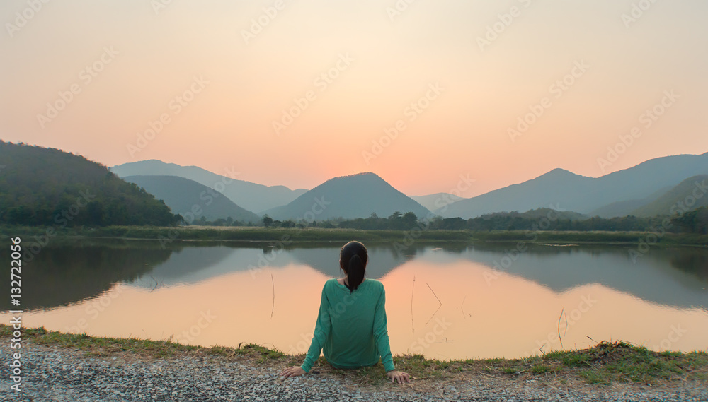 Fototapety, obrazy: An Asian woman seeing sunset thoughtfully by the lake
