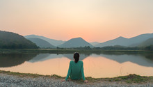An Asian Woman Social Distancing In Sunset By The Lake