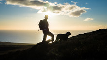Silhouettes Of A Hiker And Two Dogs At Black Combe In The Lake District, With Sunset Over The Irish Sea
