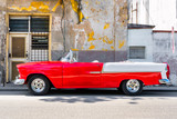 Classic red convertible car next to a shabby building in Old Havana - 132727045