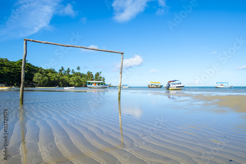 Fotografia, Obraz  Rustic football pitch made from wood on the tidal shore of a tropical Brazilian