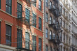 Typical building facades with fire escape stairs, sun beam in New York