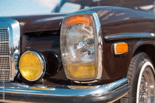 Fragment of the front of the vintage car headlights and radiator © anko_ter