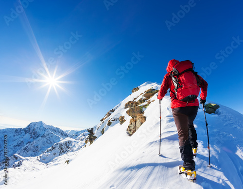 Photo Stands Mountaineering Extreme winter sports: climber at the top of a snowy peak in the Alps. Concepts: determination, success, brave.