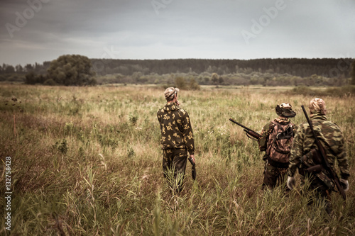 Ingelijste posters Jacht Hunters in camouflage walking through rural field during hunting season season in overcast day with moody sky