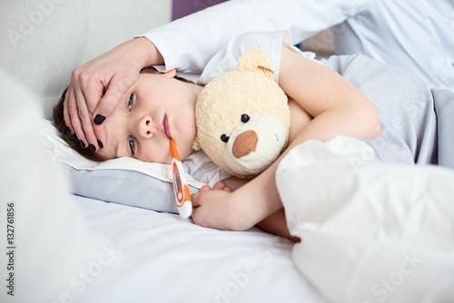 Fotografia  Sick little child with temperature in bed.