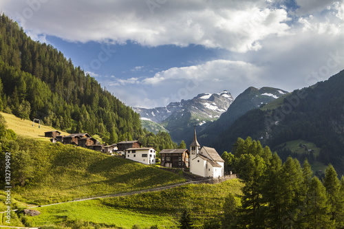 Canvastavla idyllic swiss mountain village with church in  alps in switzerland