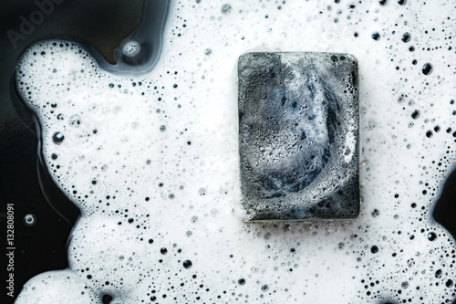 Valokuva  Black coal bar of soap in foam on dark