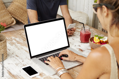 Caucasian couple using free wi-fi at cafe and enjoying