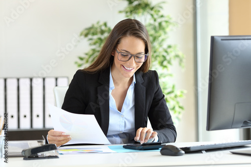 Businesswoman using a calculator at office
