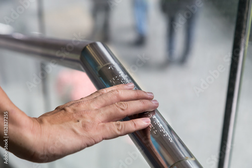 Valokuva  Hand reading Braille inscriptions for the blind on public amenity railing