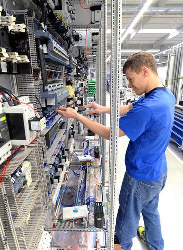 Poster Industrial geb. Montage von Elektronik in einer Fabrik - junger Mann arbeitet an einem Schaltschrank // Montage of electronics in a factory