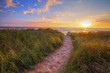 canvas print picture - Path To A Summer Sunset Beach. Winding trail through dune grass leads to a sunset beach on the coast of the inland sea of Lake Michigan. Hoffmaster State Park. Muskegon, Michigan.