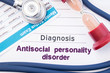 Diagnosis of Antisocial personality disorder (ASPD). On psychiatrist or psychologist table is paper with inscription Antisocial personality disorder near psychiatric report, hourglass and stethoscope