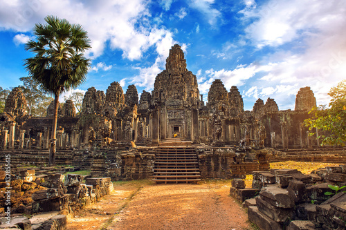 Wall Murals Place of worship Ancient stone faces at sunset of Bayon temple, Angkor Wat, Siam