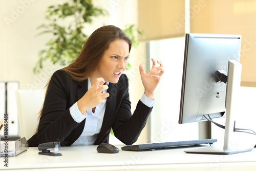 Furious businesswoman using a computer Fototapet
