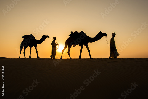 Fotografija  Rajasthan travel background - two indian cameleers (camel drivers) with camels silhouettes in dunes of Thar desert on sunset