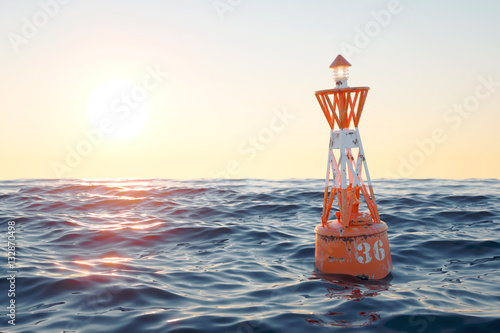 Buoy in the open sea on the sunset background. Canvas Print
