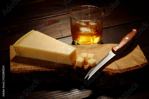 Parmesan cheese cut into cubic on a wooden board with knife and glass of whiskey on the second plan with ice
