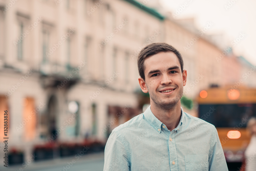 Fototapety, obrazy: Smiling young man standing in the city